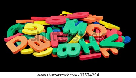 A pile of colorful foam letters isolated on black.