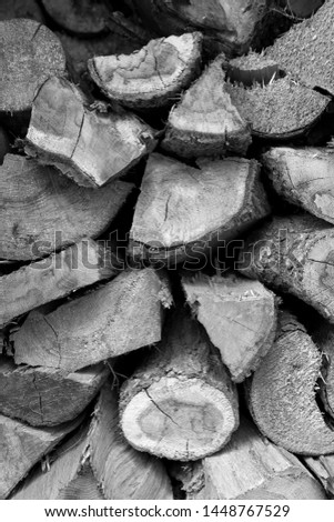 A pile of cut firewood abstract texture. Lots of stacked wooden logs piling, tightly alligned. Wallpaper, background, repetitive pattern. Lumber, timber concept. Horizontal shot, wall of wood