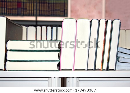 A pile of different books on a wooden shelf