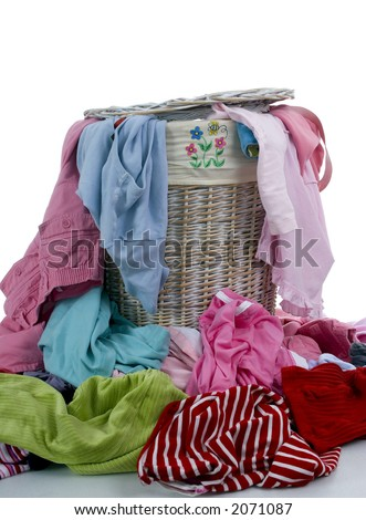 A pile of dirty clothes overflows from a young girls laundry basket