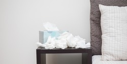 A pile of dirty, used, and crumpled up tissues on a nightstand.