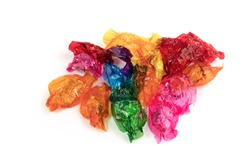 a pile of empty colorful candy wrappers isolated on white