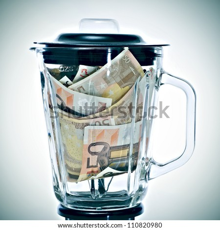a pile of 50 euros bills in a blender symbolizing the euro devaluation - stock photo