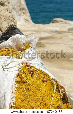 A pile of fishing nets stored in a nylon sack by the sea