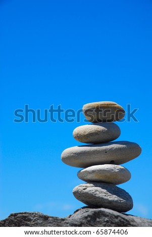 A pile of five big grey pebbles on a rock in front of blue sky background.