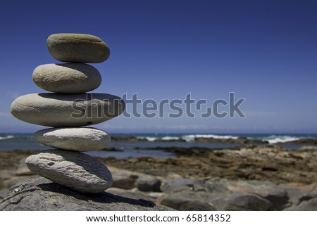 A pile of five big grey pebbles on a rock in front of blue sky background with the coast line in the background. / Zen by the sea.