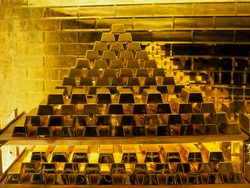 A pile of gold bars in front of a golden wall; golden ingots