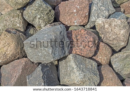 A pile of granite boulders piled on top of each other in gray, beige, and brown hues with rough edges. Natural organic mineral background with a play of light and shadow for the design.