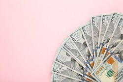 A pile of hundred dollar bills on pink background. Top view