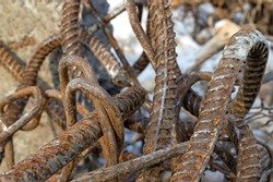 A pile of iron twisted rusty old reinforcing wire lies among the logs on the river bank 2