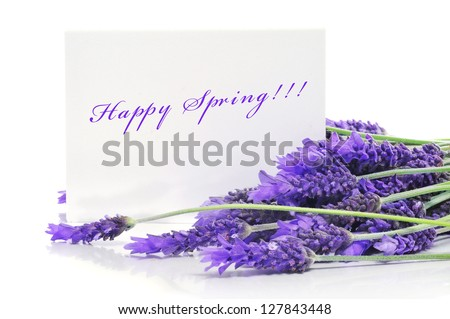a pile of lavender flowers and the sentence happy spring written in a paper label