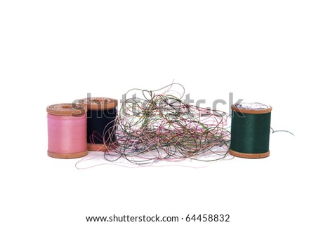 A Pile of Loose Thread and Spools on a White Background