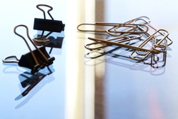 A pile of metal paper clips on a reflective glass surface. Office work concept. Macro. Selective focusing. Close-up