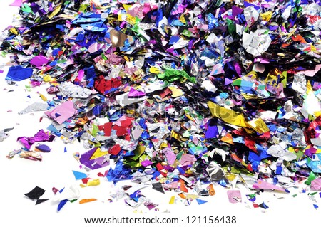 a pile of metallic confetti of different colors on a white background
