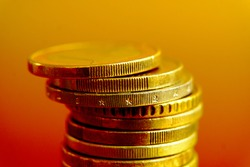 A pile of multiple golden euro coins stacked on each other. Close up saturated photo side view with blurry golden yellow red color fading background.