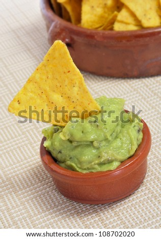 a pile of nachos and guacamole served in a restaurant