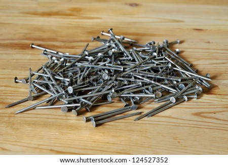 A pile of nails on a wooden surface.