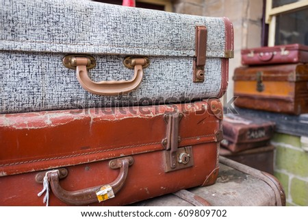 A pile of old and worn antique suitcases. #609809702