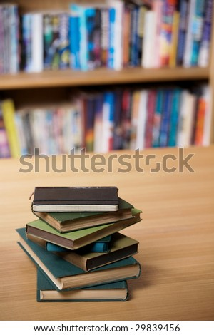 A pile of old books on a table, with shelves of books in the background.