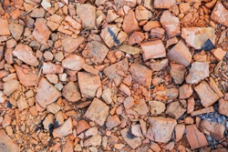 A pile of old broken red clay brick rubble after demolition of an old building lies on the ground on a building site