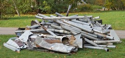A pile of old galvanized rain drain pipes lies on green  grass