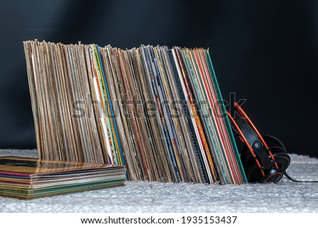 a pile of old vinyl records and hifi headphones