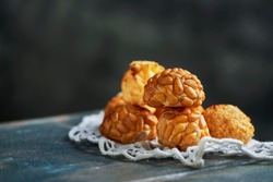 a pile of panellets, typical confection of Catalonia, Spain, eaten traditionally on All Saints Day, placed on a crocheted doily, on a gray wooden table