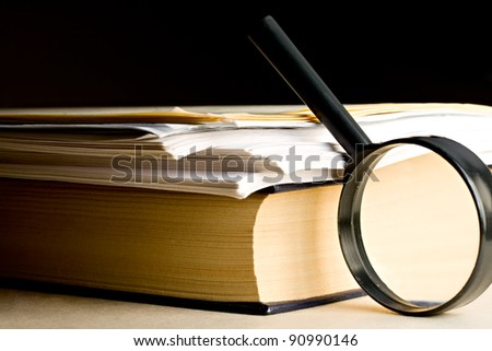 A pile of paper and a book through the magnifying glass