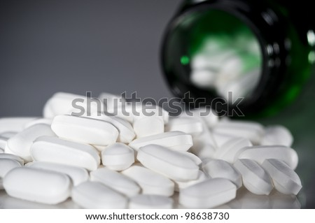 a pile of pills with bottle in background