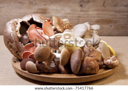 A pile of raw exotic mushrooms on a wooden plate.