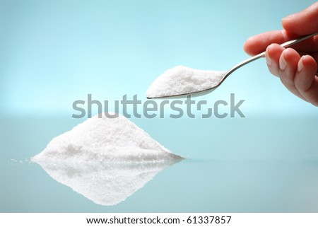 A pile of salt and a hand holding a silver spoon