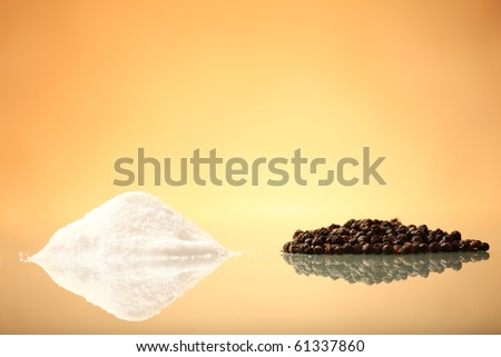 A pile of salt and pepper over warm background