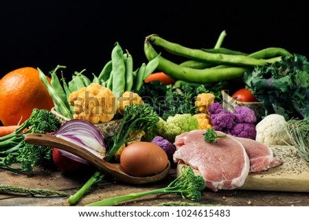 a pile of some fruit and some different raw vegetables, such as cauliflower of different colors, broccolini or french beans, and some eggs and some slices of meat on a rustic wooden table