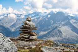A pile of stones (also called cairn, Steinmännchen or Steinmandl) in the austrian alps, used as a hiking marker. They are also found in buddhist temples and will be used as zen stones for meditation.