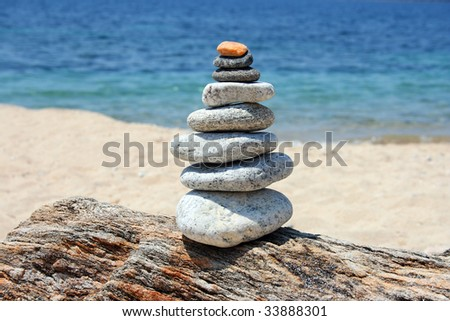 a pile of stones on a rock, the blue sea and the beach in the background