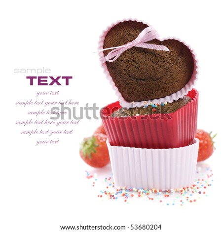 A pile of three chocolate heart shape muffins in  silicone molds with strawberry and sprinkles