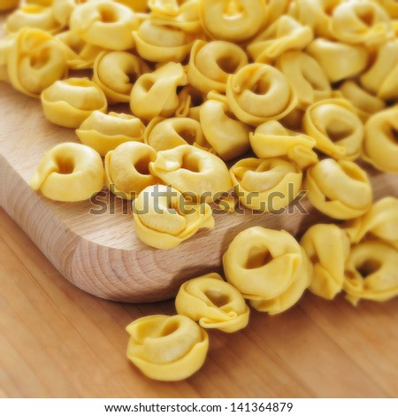 a pile of uncooked tortellini on a table, ready to be boiled