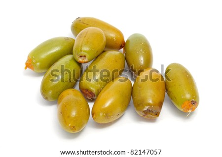 a pile of unripe dates on a white background