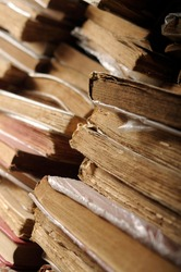 A pile of untidy old and foxed paper books in a shelf.