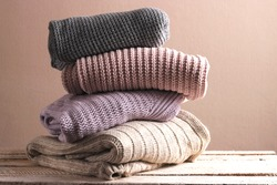 A pile of warm sweaters on a wooden table on a light background. Autumn and winter clothes.