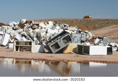 A pile of water heaters, air conditions, and other appliances at a waste dump