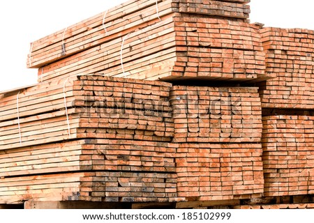 A pile of wood edged boards packed in stacks with tags size parameters for loading cranes and transport the cargo ships in the seaport