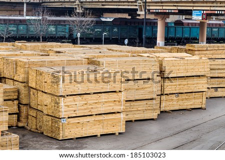 A pile of wood edged boards packed in stacks with tags size parameters for loading cranes and transport the cargo ships in the seaport and railway wagons
