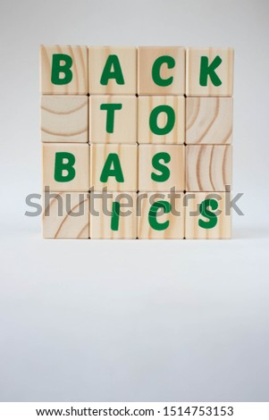 A pile of wood letter blocks forming the expression back to basics on a white background