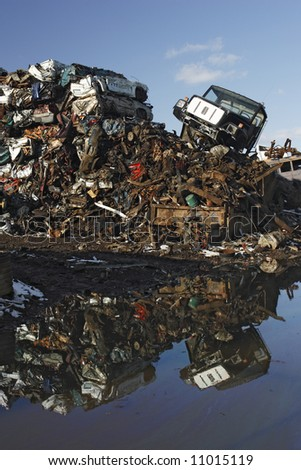 A pile of wrecked cars and trucks in a recycling operation is reflected in water.