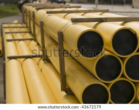A pile of yellow and black plastic construction pipes strapped together. Toronto, Ontario, Canada.