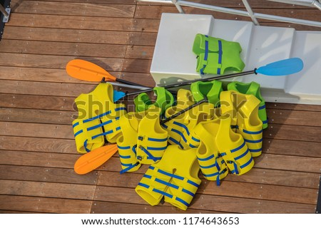 A pile of yellow and green life vests with boat paddles piled on a wooden dock and some white plastic stairs #1174643653