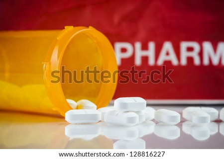 a pill bottle with prescription pills and pharmacy paper bag in the background