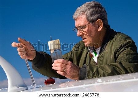A pilot checking the level of fuel in his Cessna 172-SP.
