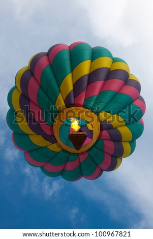 A pilot engages the burner of a hot air balloon during flight.